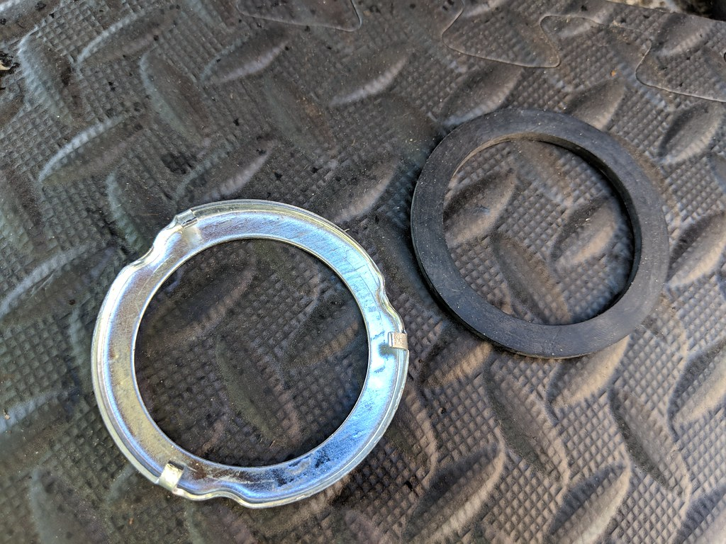 Shiny metal ring with lugs sitting on a mat alongside a matching new rubber sealing ring