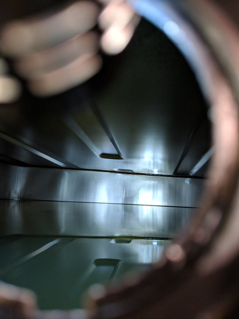 View through a hole into a fuel tank showing gleaming metal sides reflecting the torchlight
