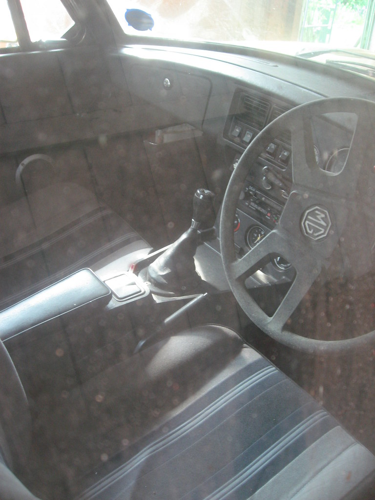 Taken through a side window the interior shows cloth seats and a black dashboard, both without any obvious marks or signs of age