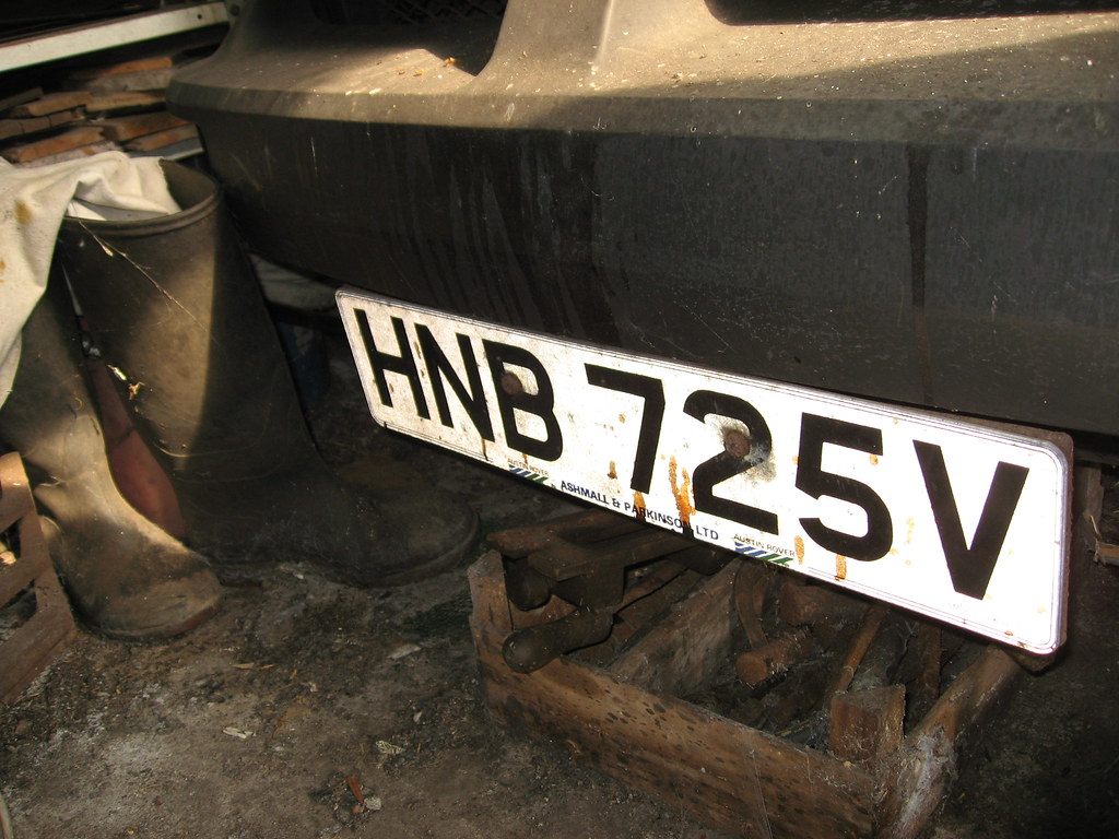 The front number plate with a box of chisels sitting under the front bumper on a dusty floor