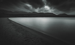 Footprints In The Sand (Iain Brooks) Tags: loch morlich long exposure black white water clouds lake scotland highlands cairngorms mountains mono leading lines