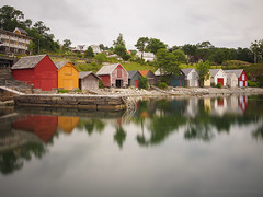 Reflections along a Norwegian fjord (RobertCross1 (off and on)) Tags: 1250mmf3563mzuiko bergen bjrnefjorden em5 europe hordaland longexposure norge norway omd olympus os osyro scandinavia solstrand architecture boathouse boats clouds fjord ladder pier reflection water no