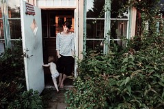 (jean_pichot1) Tags: hanna shadows bright yellow golden stripes open plants leaves overgrown garden leaning standing reflection window smile woman doorway child sunset summer home evening country skne sweden