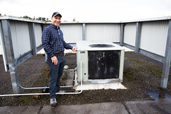 Operating Engineer, Ali Wandy, in front of an Old Heating/Cooling Rooftop Unit at the King County Environmental Lab (EE Image Database) Tags: heating cooling rooftop unit engineer
