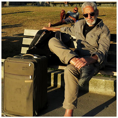 Traveler (HereInVancouver) Tags: man beard greyhair suitcase sunsetlight lifeonaparkbench vancouverswestend vancouver bc canada canong16 candid streetphotography
