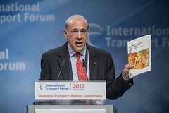 Angel Gurría gestures with an OECD study at the Congress Center Leipzig