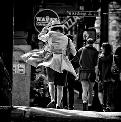 I'm in a hurry (. Jianwei .) Tags: street urban woman white black coffee hat vancouver square photography lights back waves mood dof view traffic wind walk candid coat run pizza 365 hastings moment  maninskirt handsign a500 jianwei kemily