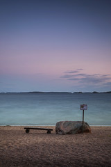 Bench at the beach (Olli Tasso) Tags: beach sea shore sand bench rock sign water blur longexposure hamina suomi finland clear sky pink glow peaceful serene calm evening summer kes august elokuu pitkvalotus meri ranta rannikko penkki kivi camping leirintalue pitkthiekat