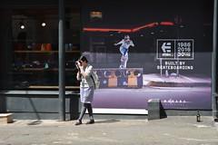 Female Photographer, Oak Street, Northern Quarter, Manchester, England. (westport 1946) Tags: england unitedkingdom manchester manchesterstreets oakstreet northernquarter shopfront manchestershops note posterdesign poster skateboardshop windowdisplay sportswearshop styledesign cityscene urbanscene text female women photographer snapper adverts streetadvertising sidewalk pavement outdoor buildings nikon5200 nikon
