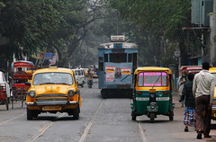 Time Travel / Kolkata, India (2012) (Stephan Rebernik) Tags: auto city trees people india streets travelling cars walking reisen asia asien cityscape traffic taxi transport tracks streetphotography pedestrian menschen transportation stadt tuktuk autos roads publictransport trams bume kolkata verkehr stdte indien gleise gehen southasia shabby streetcars schienen rudig tramways passanten strasen schbig hindustanambassador meansoftransport transportmittel ffentlicheverkehrsmittel straightroads sdasien strasenfotografie strasenbahnen stadtgebiet geradestrasen
