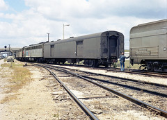 Amtrak Floridian, with locomotives from both the Miami and Saint Petersburg sections, is seen coupling baggage cars at Auburndale, Florida, mid 1970's (alcomike43) Tags: old railroad color classic vintage ties switch photo track diesel engine trains historic negative amtrak photograph rails locomotive e7 sal acl e9 e8 ballast rightofway scl dieselengine turnout mainline seaboardcoastline emd passengertrains us92 roadbed diesellocomotive highwayoverpass dieselelectriclocomotive atlanticcoastline aunit crewmen seaboardairline blocksignal eunits switchmen auburndaleflorida conventionallightweightpassengercars conventionaljointedsectionrail diamondprotectionblocksignal amtakfloridian