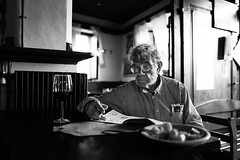 Wine, potatoes and crosswords... (Giulio Magnifico) Tags: soul leica beauty street vintage soulful emotions smile blackwhite old summilux crosswords man style portrait wood powerful leicaq beautiful udine italy happy bw book classic 28mm osteria eye mood artist life wine traditional