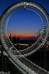 Looking through the Loop - Magic Mountain Tiger and Turtle (Yvonne Oelsner) Tags: tigerandturtle magicmountain duisburg ruhrgebiet ruhrarea rollercoaster montañarusa halde routederindustriekultur industrialheritagetrail staircase treppe landmark loop looping walkablerollercoaster rollercoastersculpture architecture blauestunde bluehour sky color contrast sonnenuntergang sunset landschaft landscape