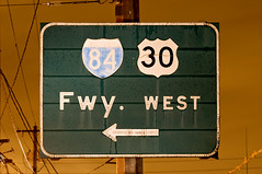 Fwy. West (Curtis Gregory Perry) Tags: road 58th street old sky orange west green wet rain sign 30 night oregon vintage square wire nikon highway long exposure glow antique telephone 85mm drop pole faded freeway signage button raindrops shield interstate arrow avenue copy rectangle dripping reflector numbered 84 d300 glisan banfield fwy