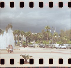 Hold my hand (Plain Bananas) Tags: sky storm love film fountain analog 35mm lomo lomography couple hand posing cyprus palmtrees diana promenade analogue dianaf larnaca sprocket larnaka foinikoudes    phoinikoudes