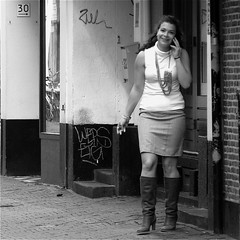 She smiles.. (Akbar Simonse) Tags: people urban bw holland netherlands girl monochrome smile square necklace boots zwartwit cigarette candid streetphotography cellphone denhaag smoking smoker thehague streetshot straat roken laarzen straatfotografie straatfoto dedoka akbarsimonse
