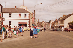 Main Street, Belturbet, Co. Cavan, 1990 (National Library of Ireland on The Commons) Tags: ireland cars coffee festival bar heineken tv video mainstreet garda wheelchair guard guinness redhead pharmacy shops cavan hifi crowds newsagent policeman aerials ulster belturbet chemist foodstore lplate touristi