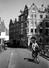 Cycling @ Amsterdam (PaulHoo) Tags: contax t2 film analog 35mm trix 2016 bw blackandwhite monochrome city urban holland netherlands architecture building amsterdam people candid streetcandid streetphotography cycling bike