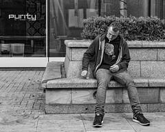 Manchester 021 (Peter.Bartlett) Tags: manchester noiretblanc olympusomdem5 unitedkingdom bench people city urbanarte text window sitting cigarette streetphotography lunaphoto man urban macro monochrome uk m43 microfourthirds smoking bw reflection sign blackandwhite peterbartlett candid england gb macphuntonality