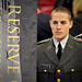 ROTC student marshall holds a banner at commencement.