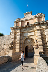 Gateway to Mdina (Alex Treadway) Tags: street door old city bridge vacation people woman sunlight holiday history stone architecture female facade walking outdoors island person town alley sandstone europe european day arch village pavement path balcony flag exploring entrance malta medieval cobblestones doorway brightlight alleyway yellowstone walls archway elegant baroque passage cobbles discovery oldtown vacations thepast oneperson clearsky oldfashioned traditionalculture mdina walledtown onepersononly traveldestinations buildingexterior placeofinterest mediterraneanculture stripeydress builtstructure malteseislands vacationdestination holidaydestinations 3034years