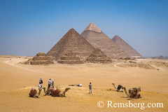 Cairo, Egypt Tourists and camel drivers with their camels resting in the desert with the three Great pyramids of Giza in the background against a clear blue sky. From left to right stands the Pyramid of Mekaure (smallest of the three), Pyramid of Khafre ( (Remsberg Photos) Tags: africa cairo middleeast egypt world travel sightseeing tourist photography ancient worldheritagesite civiliaztion history historical desert pyramid pharoh giza sahara nile khafre chephren mekaure mortuarytemple khufu vast empty desolate camel cameldriver bluesky egy