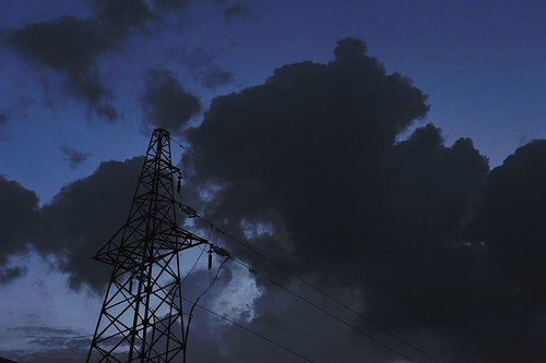electric power tower under black clouds