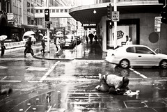 Benighted (Follow The Swallow) Tags: poverty life street people blackandwhite bw storm money cup wet rain weather june analog dark lens sadness newspaper grim coins films sydney pluie australia streetlife bum cocky alcoholism business 55mm rainy hardcore barefoot newsouthwales cbd 100 aboriginal citizen surrounded