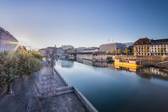 The Awakening of Geneva (Maximecreative) Tags: select geneva genve coulouvrenire switzerland suisse longexposure reflections water river rhne statue dawn sunrise flare quai docks calmness city still calm serene tree perspective summer urban cityscape blue