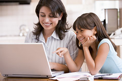 Woman and young girl in kitchen with laptop an...