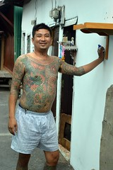 tattooed young man (the foreign photographer - ) Tags: 30jul16nikon tattooed young man leaning building shrine khlong thanon portraits bangkhen bangkok thailand nikon d3200