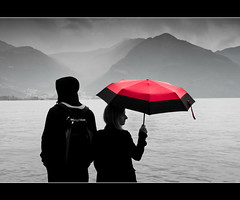Lovere behind her red umbrella (susivinh) Tags: red italy lake mountains water monochrome umbrella lago grey gris monocromo rojo agua couple italia pareja paraguas lombardia montaas lombardy