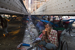 A homeless cycle rickshaw driver smokes underneath a bridge at a parking lot next to the Yamuna River where he sleeps (ActionAid UK) Tags: poverty urban india man colour cigarette delhi indian smoke homeless transport poor rickshaw newdelhi destitute