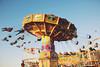 Carnival (Amanda Mabel) Tags: carnival blue light sky people stilllife childhood vintage happy flyer ride bright sunny carousel spinning amusementpark rollercoaster cheerful royalsydneyeastershow amandamabel