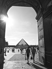 Louvre Pyramid (vieweronline) Tags: street people blackandwhite bw sun paris france monochrome contrast pyramid noiretblanc louvre streetphotography silhouettes nb panasonic flare pyramide twopeople candidshots m43 pyramidedulouvre parisiens urbanshots photosderue gx1 carryingabag microfourthirds