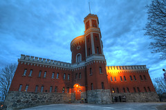 The Citadel (Henrik Sundholm.) Tags: door flowers trees building brick tower castle sign stone clouds lights parkinglot exterior sweden stockholm dusk citadel sverige lamps flagpole trashcans fortress hdr monarchy kastellet ashtrey historicallandmark castellations kastellholmen royalism