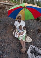 Mother and baby selling charcoal, Cyamudongo area - Rwanda (Eric Lafforgue) Tags: africa woman umbrella outdoors african femme rwanda charcoal afrika commonwealth parapluie afrique motherandbaby eastafrica africaine charbon ombrelle blackskin lookingatcamera ruralscene centralafrica 2240 kinyarwanda ruanda peaunoire afriquecentrale   regardcamera   republicofrwanda   ruandesa mereetbebe