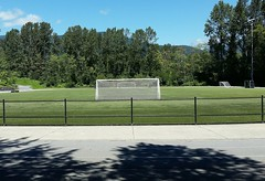 Sunny Sunday soccer pitch (walneylad) Tags: sutherlandsecondaryschool grandboulevard northvancouver britishcolumbia canada soccerpitch playingfield grass goalposts fence track field trees summer july sunday bluesky clouds mountains view scenery shade sun space
