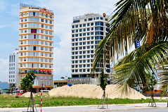Hotel central (Roving I) Tags: hotels architecture tourism travel palmtrees trees sand piles heaps buildingsites cicilia nhatninh buses coaches danang vietnam
