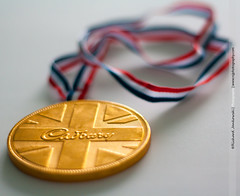 [125/365] Taste of Gold (Rich Jankowski) Tags: blue red england white canon eos rebel 50mm gold kiss unitedkingdom chocolate top award best medal cadbury novelty photoaday winner gb ribbon 365 olympics goldmedal firstclass thebest 50mmf18 rebelxs 1000d canon1000d noveltyaward 2012inphotos