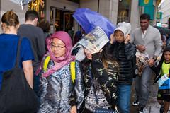 Free newspapers (Gary Kinsman) Tags: 2016 london w1 westend candid streetphotography streetlife fujix100t fujifilmx100t raining rain wet dark flash slowsync slowsyncflash movement motion motionblur jacket shelter tottenhamcourtroad newspapers