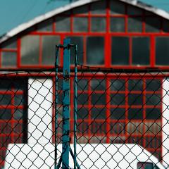 Red factory (hinterland) (sandroraffini) Tags: fabbrica hinterland factory red blue fence urban details exploration white square moche blurred lavoro work abstract reality peek private property propriet privata no trespassing vietato entrare bologna villanova castenaso sandroraffini everiday life canon 70200
