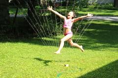 Leap!  Delight!  Heat begone! (stickyhipp) Tags: grandma green wet water grass swimming ma lexington grandpa hose sprinkler heat leap humid