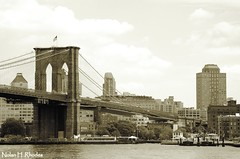 Famous Historical Landmark Picture Of Brooklyn Bridge by Nolan H. Rhodes (nrhodesphotos(the_eye_of_the_moment)) Tags: park nyc trees windows bw brick clock metal stone sepia architecture brooklyn clouds landscape pier dock waterfront steel towers scenic americanflag landmark cables fultonferrylanding brooklynbridge eastriver suspensionbridge watchtower buidlings roadway treatment downtownbrooklyn nrhodesphotosyahoocom wwwflickrcomphotostheeyeofthemoment dsc5426nhr