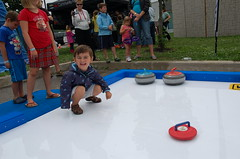Cameron throws a stone during a game of curling at the Fergus Highland Games