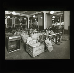 'London Postal School. Parcels office with Chute to Railway.' - Lantern Slide (British Postal Museum & Archive) Tags: mail postoffice railway chute gpo lps generalpostoffice sortingoffice lanternslide mailbag mailbags wickerbasket southplatform londonpostalschool