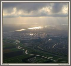 Beverwijk at sunset (Marc Geuzinge Photography) Tags: sunset holland nature netherlands beauty clouds flying europe nederland aerial photograph sunrays sunbeams noord beverwijk ijmuiden velsen northholland noordzeekanaal geuzinge marcgeuzingephotographymarc