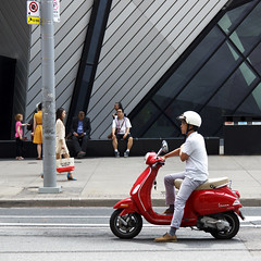 Go? (Ben Aerssen) Tags: vespa scooter male man red street road sidewalk pole curb line lines glass metal rubber tire fibreglass helmet woman bag sitting white grey gray orange yellow black asphalt toronto