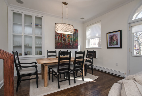 white walls ac air conditioning art lighting dining room family dinner black chairs wooden table cabinet colorful wood flooring area rug paint painting modern inviting doorway glasses picture sunny bright light home