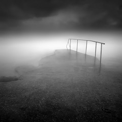 from here to eternity (Julia-Anna Gospodarou) Tags: longexposure winter sea blackandwhite bw mist seascape water monochrome strange fog clouds square pier nikon rocks moody foggy noone athens highlights le dreamy handrail unreal 2012 hoya darksky nd400 nohorizon nd8 vravrona streaksofclouds bw106 softsea sliksprintproii juliaannagospodarou siruik20x nikond7000tamron tamronaf18270mm3563pzd